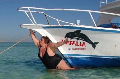 Eine dicke Frau hängt als Galionsfigur vor einem Boot.
