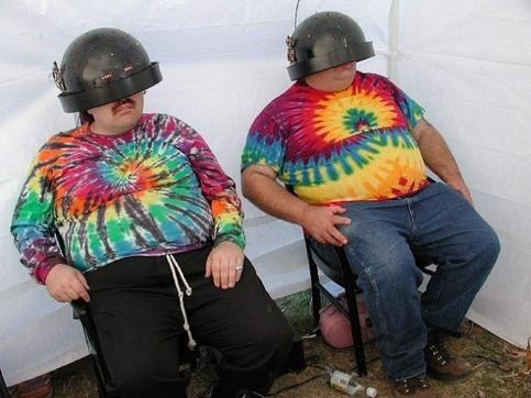 Zwei dicke Männer sitzen in Batik-T-Shirts-unter elektronischen Hauben.