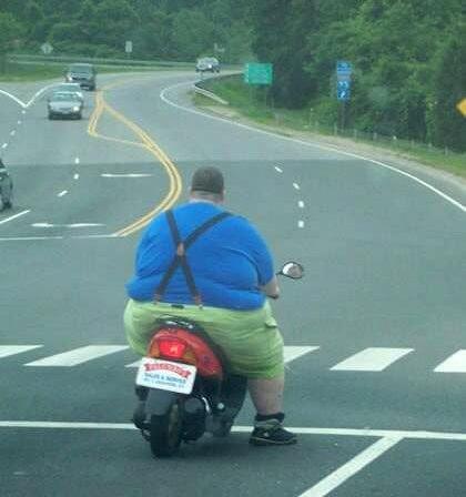 Ein dicker Mann auf einem Roller.