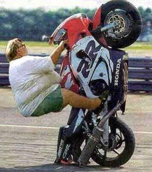 Ein dicker Mann setzt durch sein Gewicht mit seinem Motorrad hinten auf (Wheely).