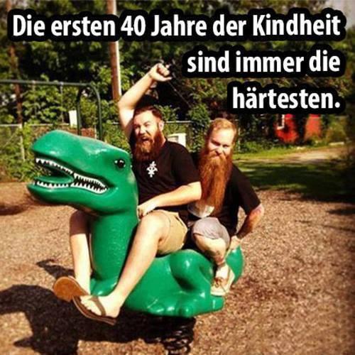 Zwei Männer mit langen Bärten reiten auf einer Dinosaurier-Wippe für Kinder auf einem Spielplatz.