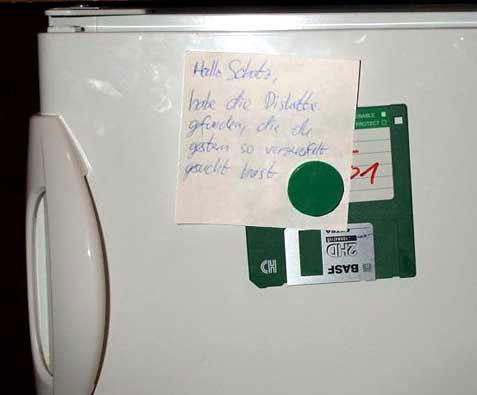"""Eine Diskette ist mit einem Magneten an einem Kühlschrank befestigt, auf einem Zettel steht """"Hallo Schatz, habe die Diskette gefunden, die du gestern so verzweifelt gesucht hast."""""""