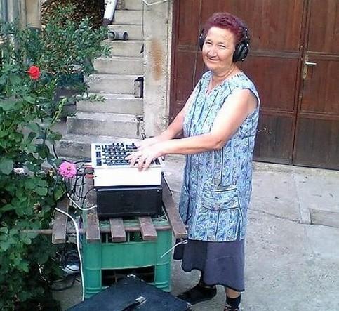 Eine Oma steht an einem DJ Pult.