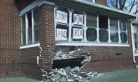"""Ein Auto ist offensichtlich in ein Haus gefahren. In der Wand des Hauses ist ein Loch und es hängen Zettel im Fenster: """"Don't drink and drive""""."""