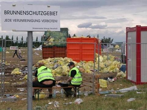"""Ein völlig verdrecktes Gelände mit einem Schild """"Brunnenschutzgebiet""""."""
