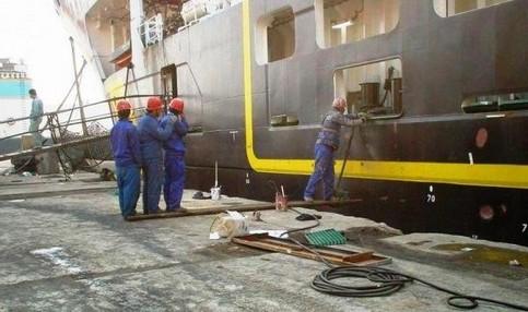 Ein Mann arbeitet an der Außenseite eines Schiffs. Er steht auf einer Bohle. Damit er nicht ins Wasser kippt, stehen drei andere Männer auf der anderen Seite der Bohle.
