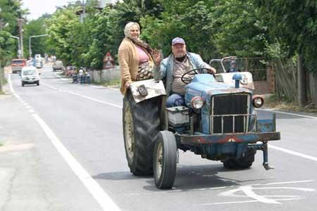 Ein Traktor mit zwei lustigen Bauern und nur drei Reifen.