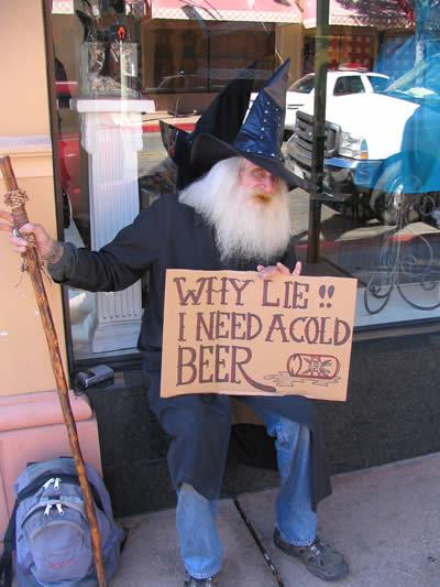 """Ein Mann bettelt in einem Kostüm, auf einem Pappschild steht """"Why lie, I need a cold beer!"""""""