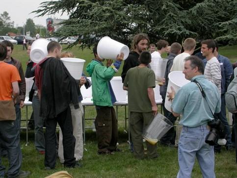 Menschen trinken Bier aus riesengroßen Bechern.