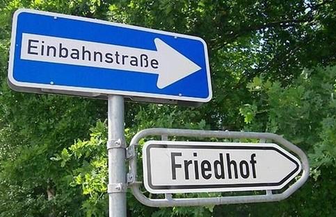 Zwei Schilder, die in dieselbe Richtung zeigen: Einbahnstraße und Friedhof.