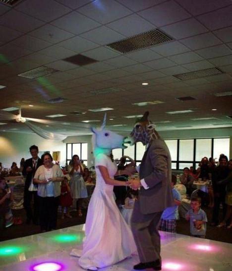 Auf einer Hochzeit tanzen Braut und Bräutigam mit Gummimasken auf dem Kopf. Sie ist ein Einhorn, er eine Giraffe.