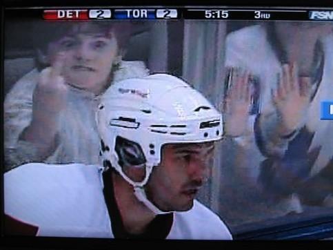 Ein Fan zeigt einem Eishockeyspieler im Hintergrund einer TV-Übertragung einen Stinkefinger.