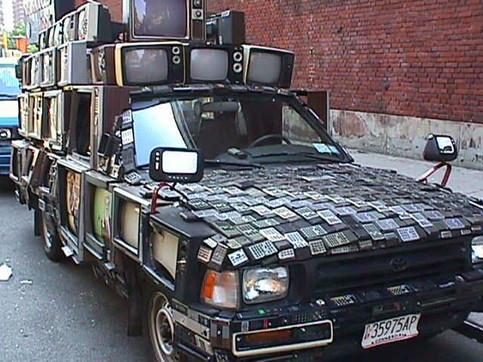 Ein Auto auf dessen Dach Fernseher, Taschenrechner, etc. befestigt sind.