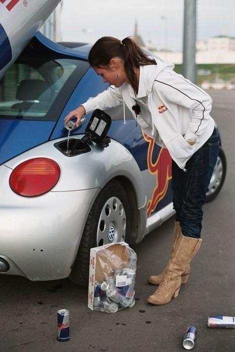 Eine Frau füllt Energy-Drinks in den Tank ihres Wagens.
