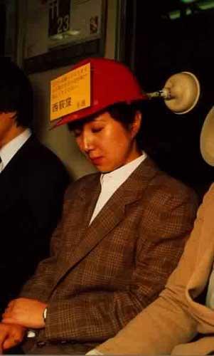Eine Chinesin, die in der U-Bahn ihren Kopf mit einem Helm an die Wand gesaugt hat und schläft.
