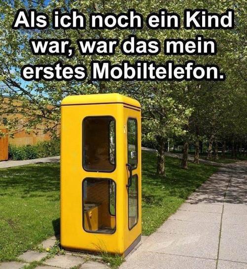 """Eine alte, gelbe Telefonzelle. Dabei steht der Text """"Als ich noch ein Kind war, war das mein erstes Mobiltelefon."""""""