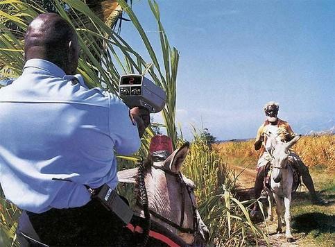 Ein Polizist blitzt einen Reiter auf einem Esel.