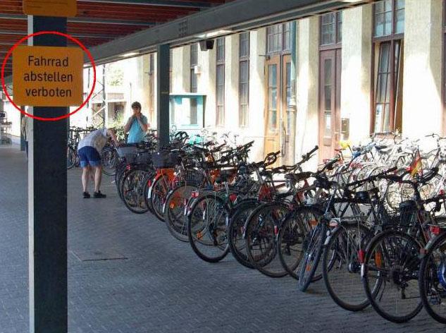 """Auf einem Schild steht """"Fahrrad abstellen verboten"""", daneben steht eine große Menge Fahrräder."""