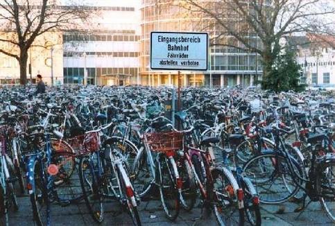 Auf einem Platz, auf dem Fahrräder abstellen verboten ist, stehen eine Menge Fahrräder.