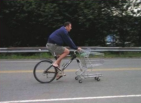 An einem Fahrrad fehlt das Vorderrad. Stattdessen wurde ein Einkaufswagen montiert und ein Mann fährt mit diesem Gefährt auf einer Straße.