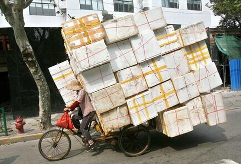 Ein Fahrradfahrer hat eine unglaubliche Menge Pakete auf seinem Fahrrad geladen.