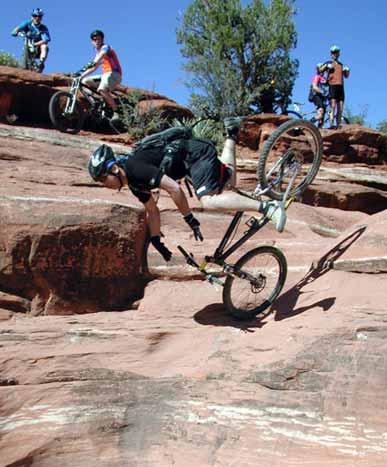 Ein Fahrradfahrer stürzt und fällt auf einen Steinfelsen.