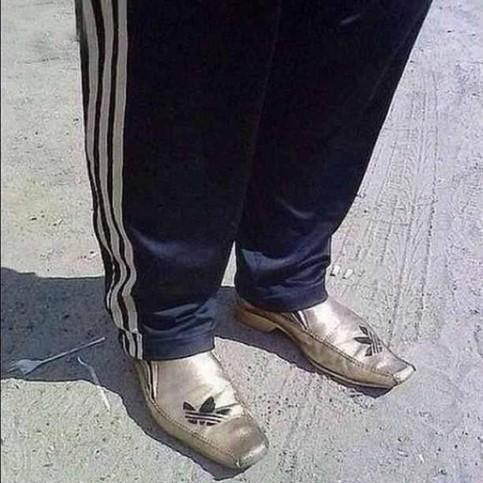 Auf zwei goldenen Schuhen ist das Logo eines bekannten Sportwaren-Herstellers aufgedruckt. Es sieht stark nach Fake aus.