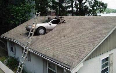 Ein Auto steckt in einem Dach fest.