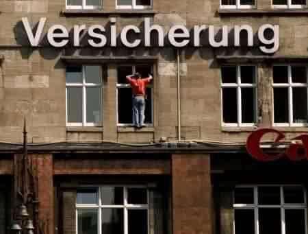Ein Mann steht auf einem Fensterbrett und putzt ein Fenster.