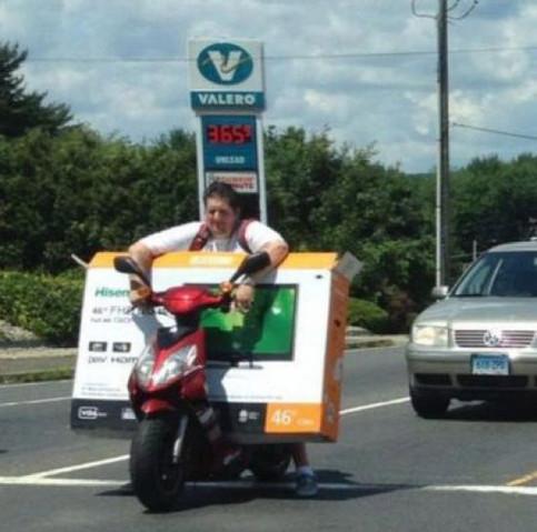 Ein Mann transportiert einen großen Flachbild-Fernseher auf seinem Roller.
