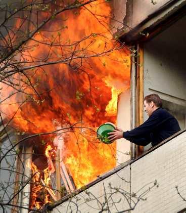 Ein Mann versucht, einen Brand mit einem kleinen Eimer Wasser zu löschen.