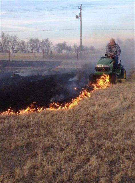 Ein Mann fährt mit einem Rasenmäher-Traktor über eine brennende Wiese. Er scheint den brennenden Rasen mit dem Traktor zu löschen.