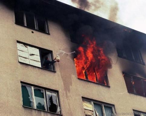 Ein Mann versucht eine brennendes Zimmer aus dem Nachbarfenster mit einem Eimer Wasser zu löschen.