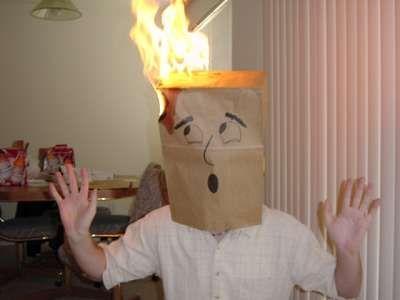 Eine Tüte, die sich ein Mann auf dem Kopf gezogen hat, brennt.