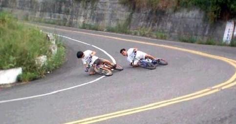 Zwei Jungen auf Fahrrädern mit extremer Kurvenlage.