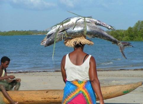 Eine Frau trägt Fisch auf dem Kopf.