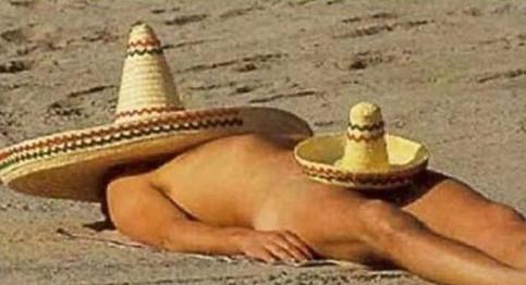 Ein Mann schläft am Strand. Dabei hat er zwei Sombrero-Hüte auf: Einen großen auf seinem Kopf und einen kleinen zwischen seinen Beinen.