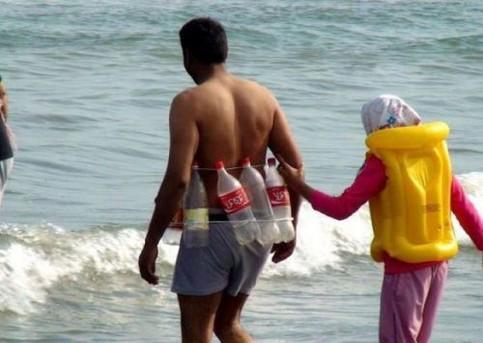 Ein Mann geht ins Meer und hat sich leere Flaschen als Schwimmweste umgebunden.