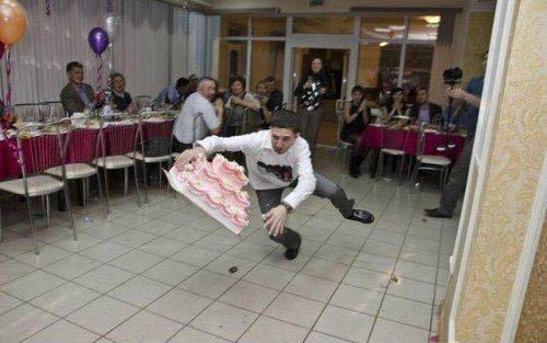 Ein Mann trägt eine Torte und fällt gerade mitsamt Torte auf den Boden.