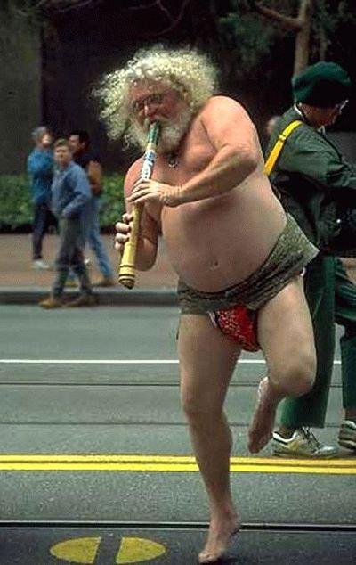 Ein Mann mit nacktem Oberkörper spielt Flöte und tanzt.