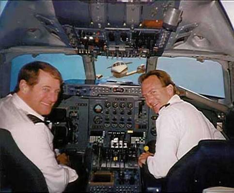 Ein Blick in ein Cockpit. Durch das Fenster sieht man ein anderes Flugzeug auf den Flieger zufliegen.