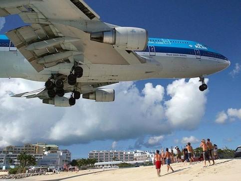 Ein Flugzeug fliegt über einen Strand am Meer.