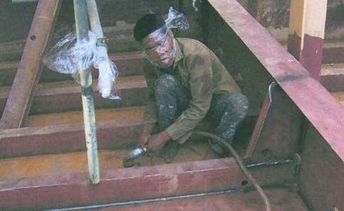 Ein Mann arbeitet mit einer Flex und hat dabei als Schutz eine Folie vor dem Gesicht.