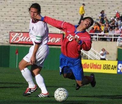 Beim Fußball macht ein Spieler eine Schwalbe, während er seinem Gegenspieler die Faust ins Gesicht schlägt.