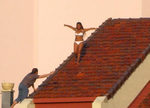Eine Frau balanciert auf einem Dach.