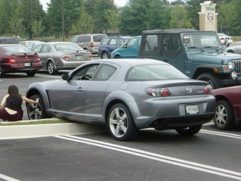Eine Frau hat ihr Auto aus Versehen auf einem Parkplatz aufgebockt.