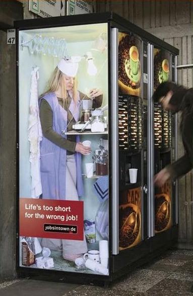 Ein Kaffeeautomat, der aussen so bedruckt ist, dass man denkt, im Inneren würde eine Kaffeefrau arbeiten und den Kaffee von Hand kochen.