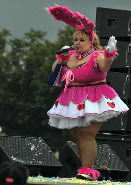 Eine sehr korpulente Frau ist als Funkenmariechen verkleidet und nimmt an einem Karnevalsumzug teil.