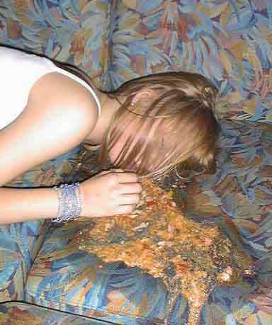 Eine Frau kotzt auf ein Sofa.