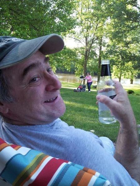 Eine Mann sitzt auf einer Bank und hält fröhlich eine leere Flasche Bier in der Hand. Im Hintergrund sieht man seine Frau rasenmähen.